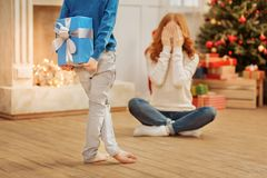 Excited mother waiting for her christmas gift. Can I open my eyes already. Selective focus on shy little box hiding a lovely present behind his back while Royalty Free Stock Photos
