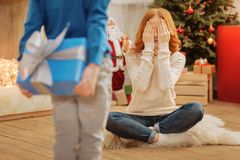Excited mother smiling while receiving christmas gift from son. Can I open my eyes now. Selective focus on an amazed mature lady closing her eyes with excitement Royalty Free Stock Photography