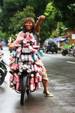 Can man. Enthusiastic man in Indonesia giving thumbs up to the camera while sitting on his motorcycle that is decorated with empty cans Stock Photos