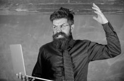 Can not get used to modern technology. Teacher bearded man with modern laptop chalkboard background. Hipster teacher. Aggressive with laptop goes mad about stock photos