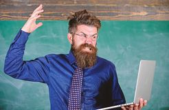 Can not get used to modern technology. Teacher bearded man with modern laptop chalkboard background. Hipster teacher. Aggressive with laptop goes mad about stock photography