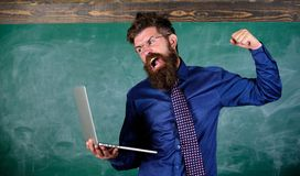 Can not get used to modern technology. Technology blows his mind. Teacher bearded man with modern laptop chalkboard. Background. Hipster teacher aggressive with royalty free stock photography