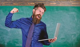 Can not get used to modern technology. Technology blows his mind. Teacher bearded man with modern laptop chalkboard. Background. Hipster teacher aggressive with royalty free stock image