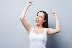 Can not hide her emotions. Beautiful young woman keeping arms raised and smiling while standing against grey background Stock Photos