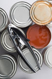 Can Opener on Tin Cans Beside Opened Can Stock Photography