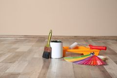 Can of paint and decorator tools on wooden floor indoors. Space for text stock photography