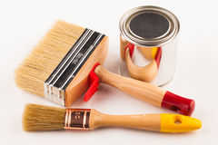 Can of paint with paintbrushes on wooden table Royalty Free Stock Image