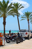Can Pastilla seaside. CAN PASTILLA, MAJORCA, BALEARIC ISLANDS, SPAIN - JULY 28, 2015: Can Pastilla seaside street with parked cars and motorcycles, palm trees Royalty Free Stock Photography