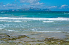 Can Picafort beach in April. Sunny beach with waves and turquoise ocean in Can Picafort in April. Mallorca, Balearic islands, Spain Royalty Free Stock Photos