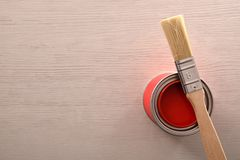 Can of red paint opened with brush over on table. Can of red paint opened with brush over on a wooden table. Top view. Horizontal composition stock photography