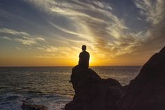 Man looking to the horizon. We can see a man who is looking at the horizon of the sea while the sun reflects, thus causing his shadow Royalty Free Stock Photos