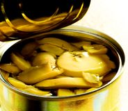 Can of sliced mushrooms. Open tin can of sliced mushrooms. Golden tones, high contrast Stock Photo