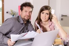 We can`t afford all this taxes.  too many bills to pay!. Scared and desperate couple holding bills to pay Royalty Free Stock Photos