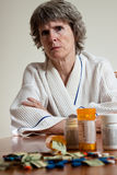 Can't afford medication concept. Mature woman with prescription medication and money in-front of her. Expensive medication. Sad patient stock photos