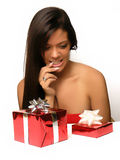 Can't Decide. Beautiful young woman choosing between two gifts, one bigger than the other, wrapped in red shiny paper.  Model is sitting behind the two gift with Royalty Free Stock Photo