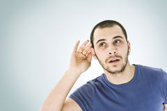 Can't hear you!. Young man with hand on ear - what did you say Stock Images