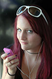Can't hear you. Pretty teenager with magenta hair listening to ipod royalty free stock photography
