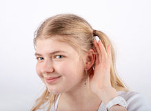 Can't hear you. Beautiful blonde girl can't hear you - she cupping hand behind her ear and smiling Stock Photography