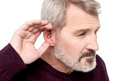 Can't hear you, what did you say ?. Mature man cupping his hand behind ear Royalty Free Stock Photography