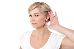 Can't hear you, what did you say?. Woman with hand behind her ear and listens carefully Royalty Free Stock Image