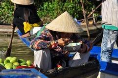 Vietnamese woman eating. Floating Market, Vietnam royalty free stock images