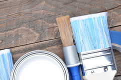 Can of white paint brushes and masking tape. On old boards Stock Photography