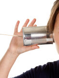 Can and wire phone. Female hand making a phone call through a can and wire stock image