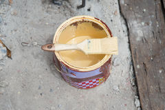 Can of yellow paint and professional brush on ground Royalty Free Stock Photo