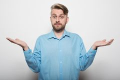 Can you believe it? Frustrated mature man in shirt looking at camera and gesturing while standing against white wall.  Stock Photo