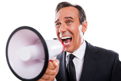 Can you hear me?. Furious mature man in formalwear shouting at megaphone while standing isolated on white background Royalty Free Stock Photos