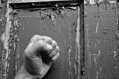 Can you hear me knocking?. Black and white fist pounding on a weathered old door Stock Image