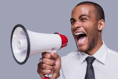 Can you hear me now?. Furious young African man in formalwear shouting at megaphone while standing against grey background Royalty Free Stock Photography