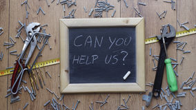 Can you help us. ? written on a chalkboard next to handyman tools Royalty Free Stock Images