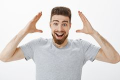 Can you imagine I got job. Charismatic joyful and excited handsome male model with beard in grey t-shirt raising hands royalty free stock image
