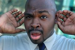 Can you repeat that please?. Did I stutter?  Young man pretending not to be hearing his boss' instructions Stock Photos