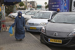Cana Gallilee Woman. An Arab woman walks along a sidewalk past parked cars in Kefer-Kenna near Nazareth in Israel, the traditional area of Cana of Gallilee Royalty Free Stock Images