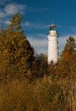 Cana Island Lighthouse. The beautiful Cana Island Lighthouse stands tall against a blue sky amidst golden autumn foliage stock photos