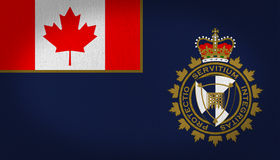 Canada Border Services Agency flag. With the canadian flag in the first quarter of it, with a big shield logo in the bottom right side, crown in golden and red Royalty Free Stock Photo