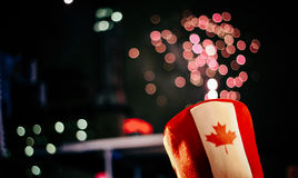 Canada Day. The top of a Canadian flag decorated hat in front of fireworks on Canada Day, 2013 Royalty Free Stock Images