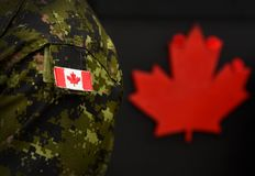 Free Canada Day. Flag Of Canada On The Military Uniform And Red Maple Leaf On The Background. Canadian Soldiers. Army Of Canada. Canada Royalty Free Stock Photos - 164210578