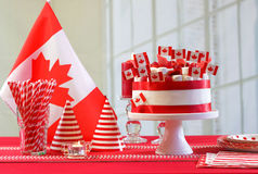 Canada Day national holiday celebration party table. With showstopper cake and flags stock photos