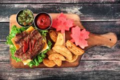 Canada Day picnic scene with maple leaf hamburger on paddle board. Canada Day picnic scene with maple leaf shaped hamburger and watermelon on a paddle board over Royalty Free Stock Images