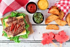 Canada Day picnic scene with maple leaf hamburger and watermelon. Canada Day picnic scene with maple leaf shaped hamburger, watermelon pops and potato wedges Royalty Free Stock Photo