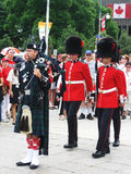Canada Day Piper and Guards, in Ottawa. A piper play bagpipe and two guards on Canada Day in front of National War Memorial in Ottawa, Ontario, Canada Stock Image