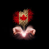 Canada day. Welcome to Canada. Fireworks in male hands in a heart shape with the Canada flag on a black background. Canada day. Welcome to Canada Royalty Free Stock Photography