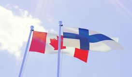 Canada and Finland, flags waving against blue sky Stock Image