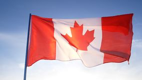 Canada flag on clear blue sky stock image