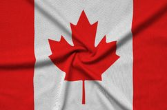 Canada flag is depicted on a sports cloth fabric with many folds. Sport team banner royalty free stock photos