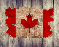 Canada flag in form of torn vintage paper. On wooden background Stock Image