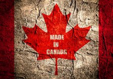Canada flag maple leaf on grunge backdrop Stock Images